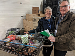 Volunteers with grocery cart of food to donate